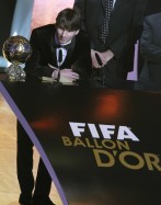 Messi of Argentina FIFA World Player 2010 stands nexthis trophy during the FIFA Ballon d'Or 2010 soccer awards ceremony in Zurich