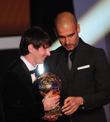 Argentina's Lionel Messi (L) is awarded